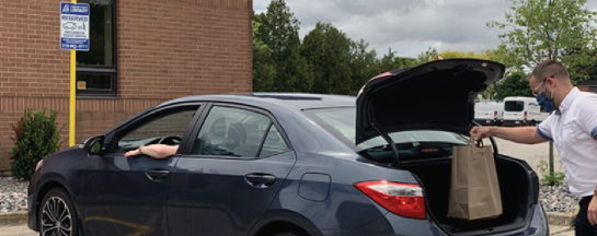 Photo of man putting book order in the trunk of a car.