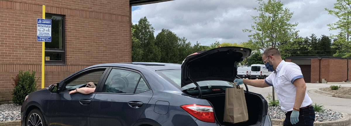 Library staff putting books in trunk of car.