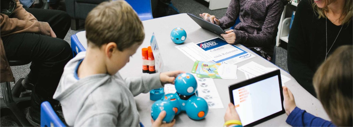 Children sitting at table with the Dash and Dot robotics.