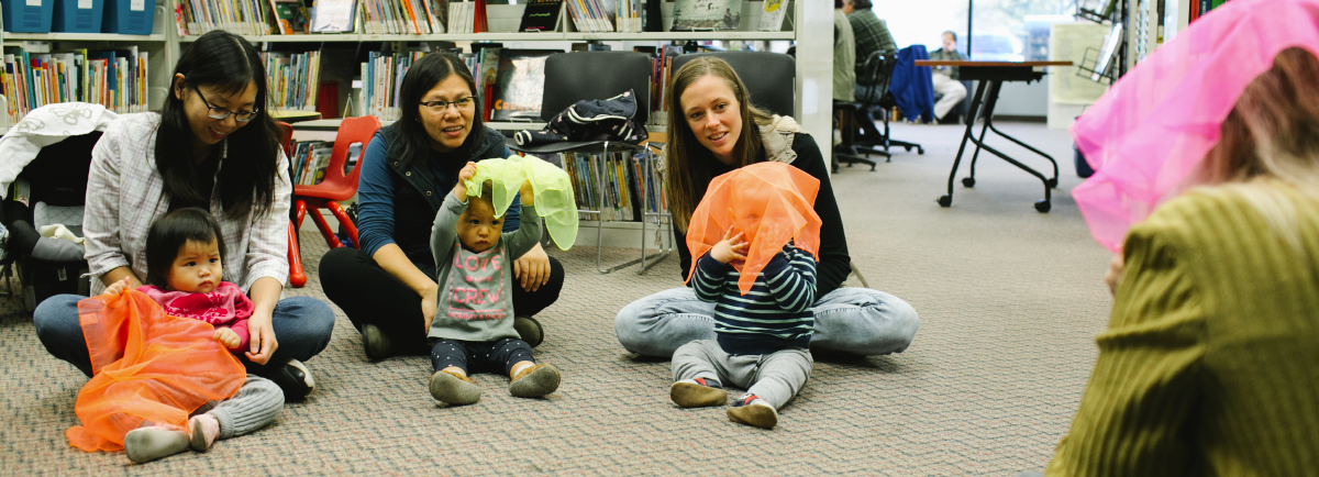 Three babies playing with their parents at the library.