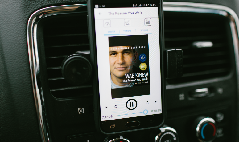 eBook on screen of phone sitting on car dashboard.