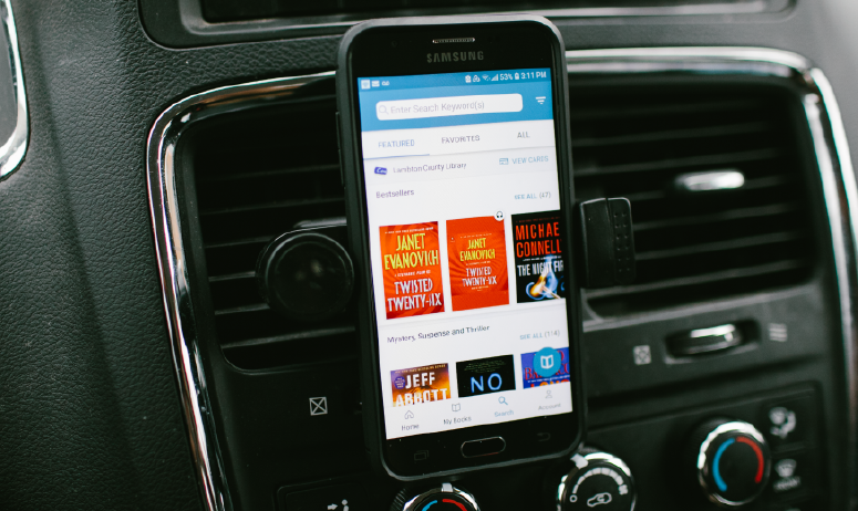 Phone on dashboard of car with book app on screen.