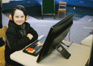 Child with headphones on sitting at a desktop computer.